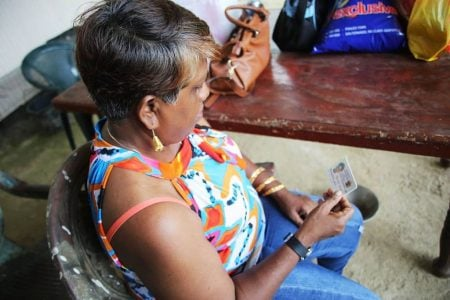 Linda Boodoo looks at the identification photo of her son Kenrick Joseph Morgan 17, a form five student of Grand Chemin Moruga , who went missing at sea and is feared kidnapped along with his cousin Kendell Singh. Photo by Vashti Singh