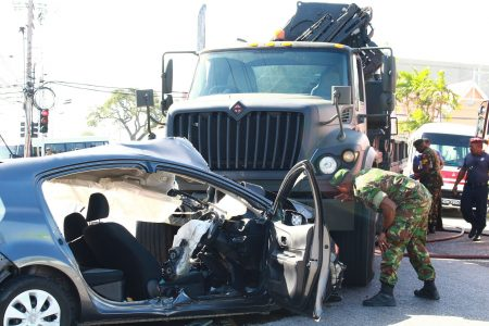 A soldier looks at the wrecked army truck which was involved in an accident at the intersection of the Priority Bus Route and Pasea Main Road, Tunapuna, yesterday.