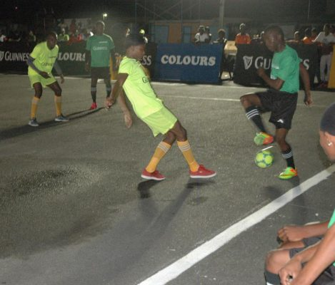 Leo Lovell [centre] of Up-Top-Bosses, in the process of challenging a Boom Bang player for the ball during the opening clash in the Guinness 'Greatest of the Streets' West Demerara/East Bank Demerara Zone at the Pouderoyen Tarmac