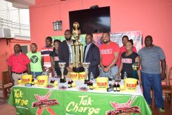 Tournament coordinator Esan Griffith collecting the championship trophy from Director of Sports Christopher Jones following the launch of the 2nd Annual Magnum Mash Futsal Championship yesterday at the Windjammer Hotel, Kitty. Also in the photo are representatives of Ansa McAl and players from several competing teams.