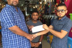 Ryan Singh (right) hands over the sponsorship cheque to BCB President Hilbert Foster in the presence of BCB PRO Simon Naidu.