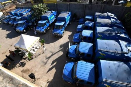 An aerial view of 11 of the 12 new trucks acquired by the Ministry of Local Government and Community Development to boost the capacity of the National Solid Waste Management Authority to handle garbage collection.