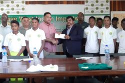 Dave Narine (right) hands over the sponsorship cheque of the 2019 GCB/Dave West Indian Imports Inter-County Under-15 tournament to Guyana Cricket Board's Anand Kalladeen in the presence of some of the players and officials