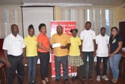 Wilton Spencer, Head of the Special Olympics Committee receives the sponsorship pact from Louanna Abrams, Sponsorship Manager at Digicel in the presence of the athletes, coach and Digicel's Communication Manager, Vidya Sanichara.