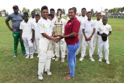Demerara Cricket Board's Kavita Yadram presents the 2019 Demerara Cricket Board U15 Inter-Association trophy to Georgetown skipper, Alvin Mohabir in the presence of the other members of the team.