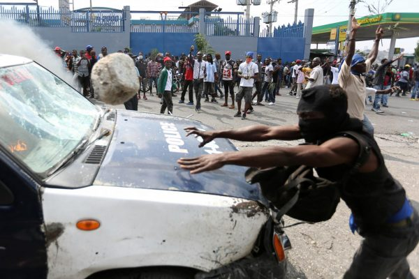 A demonstrator throws a rock at a police car during a protest against former government officials accused of misusing Petrocaribe funds and the country's inflation rate in Port-au-Prince, Haiti February 7, 2019. REUTERS/Jeanty Junior Augustin