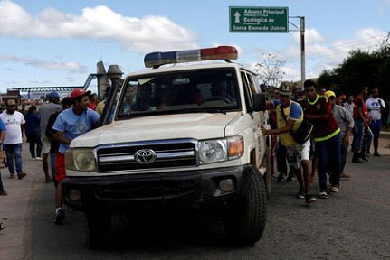 An ambulance carrying people that were injured during clashes in the southern Venezuelan town of Kumarakapay, near the border with Brazil, is assisted by people at the border between Venezuela and Brazil, in Pacaraima, Roraima state, Brazil February 22, 2019. REUTERS/Ricardo Moraes