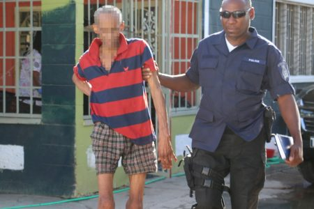 A police officer escorts one of the rescued residents from the senior citizens home in Arima yesterday.