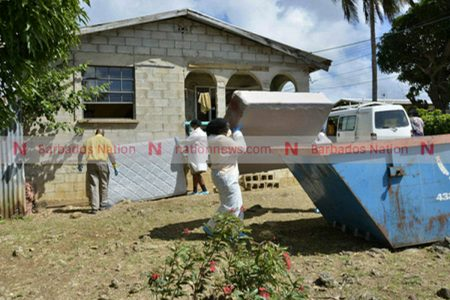 Personnel from a cleaning agency disposing of a bloody bed base yesterday afternoon.(Pictures by Lennox Devonish.)