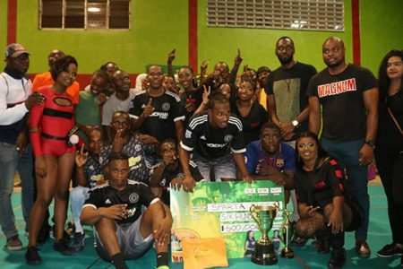 The victorious Sparta Boss team pose with their spoils after overcoming Back Circle in the finale of the NSC/Magnum Mash Cup Futsal Championship at the National Gymnasium. Present in the photo are Director of Sports Christopher Jones [3rd from right] and Magnum Brand Manager Edison Jefford [2nd from right]