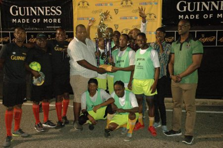 Melanie `B' Captain Ryan Seales receives the championship trophy from Banks DIH Limited representative Evlon Hendy in the presence of his team-mates following their victory over Paradise `A' in the final of the Guinness 'Greatest of the Streets' East Coast Demerara Championship. Also in the photo is Guinness Brand Manager Lee Baptiste [right]