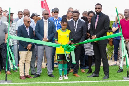 Lady Jaguars Junior National Player Aliyah Elaine [center] cuts the ribbon to officially commission the GFF's first  FIFA Forward Project following yesterday's inauguration ceremony in the presence the GFF Executive Committee, Director of Sports Christopher Jones, FIFA Director of Member Associations and Development Veron Mosgengo-Omba and participants and delegates of the FIFA Conference on Development.