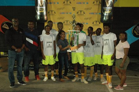 High Rollers captain Omar Brewley [center], receives the championship trophy from Banks DIH representative Romaine Adonis in the presence of his elated team-mates after they defeated  Amazings in the final of the Guinness Greatest of the Streets Linden Championship. Also in the photo are Guinness Brand Manager Lee Baptiste [left] and Linden Branch Manager Shondel Easton [right]