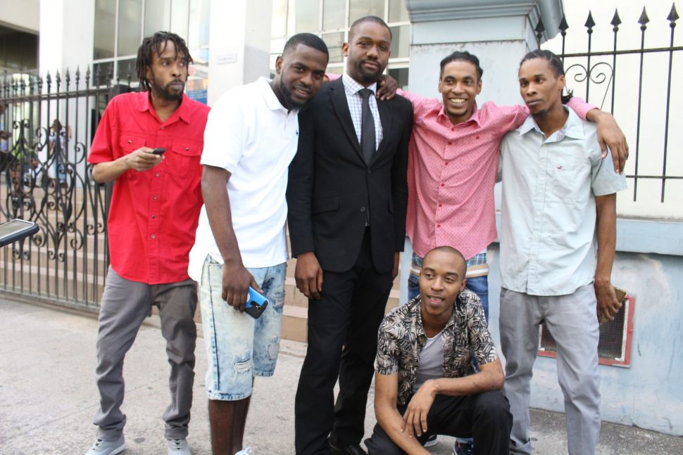Attorney CJ Williams, centre, with his clients, from left, Akili Charles, Chicki Portillo, Isreal Lara, Levi Joseph and Kareem Gomez stand outside the Port-of-Spain Magistrates Court after they were freed, yesterday.