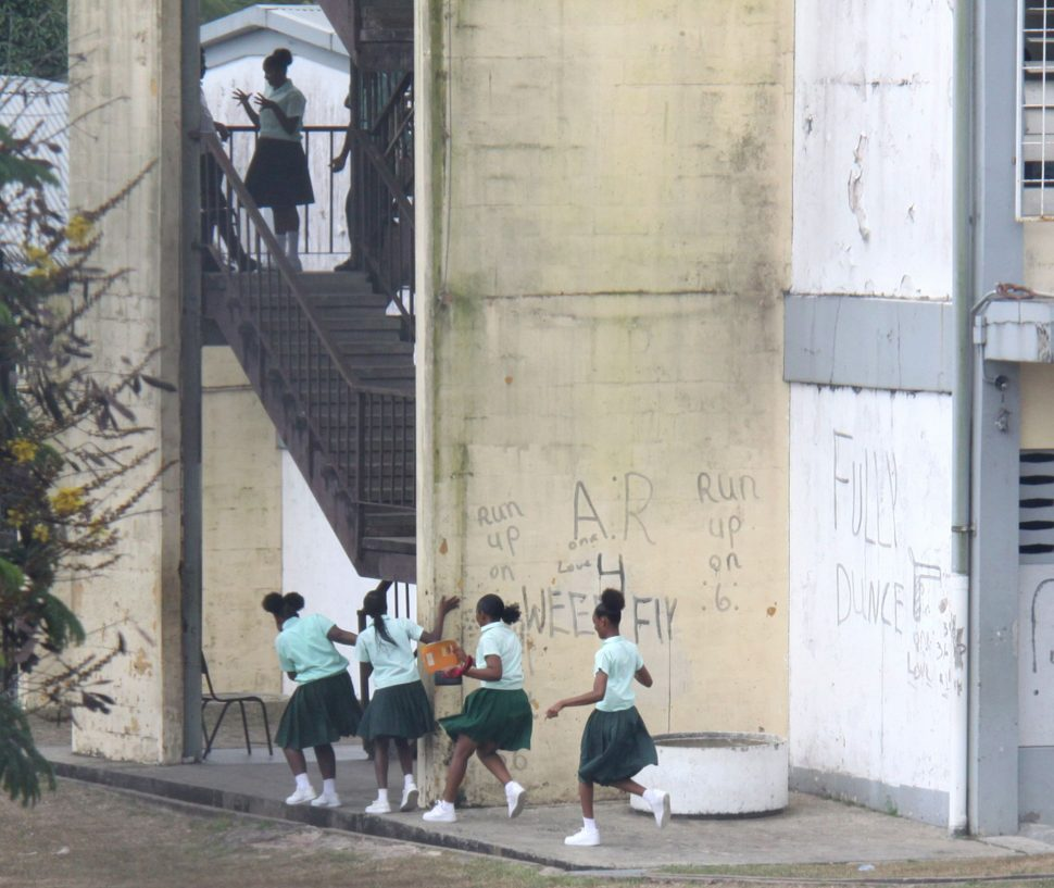 Students of Siparia West Secondary School run towards the stairway on Monday as a fight broke out in one of the classrooms above.