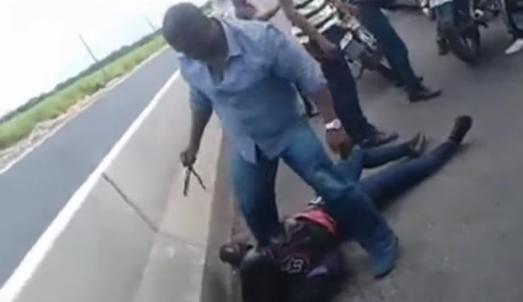 A policeman stands over the female motorcyclist after she was reportedly slammed to the ground in this screenshot from the video recording of the incident.