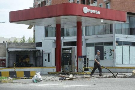 © Reuters/CARLOS EDUARDO RAMIREZ A man walks past a closed gas station of the state oil company PDVSA in San Cristobal