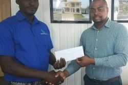 Senior Supervisor at R&D Engineering, Marvin Duke (left) hands over the sponsorship to Edison Jefford yesterday at the company's North Road Office.