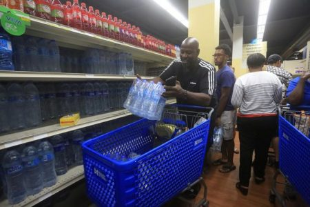 A man buys bottled water in preparation for the arrival of Tropical Storm Dorian at a supermarket in Gros Islet, St. Lucia August 26, 2019. REUTERS/Andrea de Silva