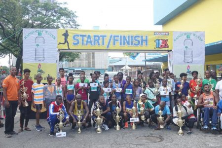 The prize winners of the ninth edition of the Courts 10k pose for photo following the event yesterday outside the company's headquarters on Main Street. (Emmerson Campbell photo)