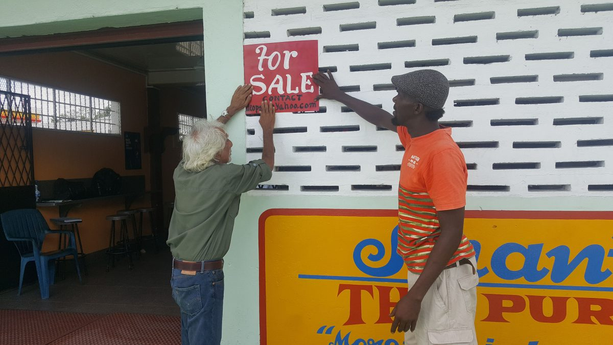 Deodat Persaud erecting a 'For Sale' sign on the building.