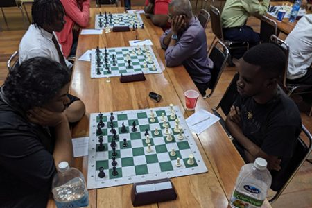 National player Taffin Khan (left) during his fourth-round match with Davion Mars at the National Resource Centre on Tuesday evening. Sitting alongside Khan is Frankie Farley (with tie), President of the Guyana Chess Federation. His opponent is national player Loris Nathoo. (Photo: John Lee)
