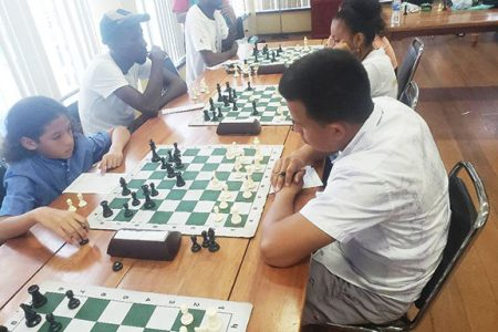 During the Gaico Grand Prix chess tournament, which ended last Sunday, children were as much in evidence as were seasoned adults and teenaged girls. At left is Joshua Khan, 6, facing Linden's Justino Da Silva. Many of the children attend Mae's Schools. Throughout the tournament, Khan was in high spirits and looked forward to playing his next opponent. (Photo: John Lee)
