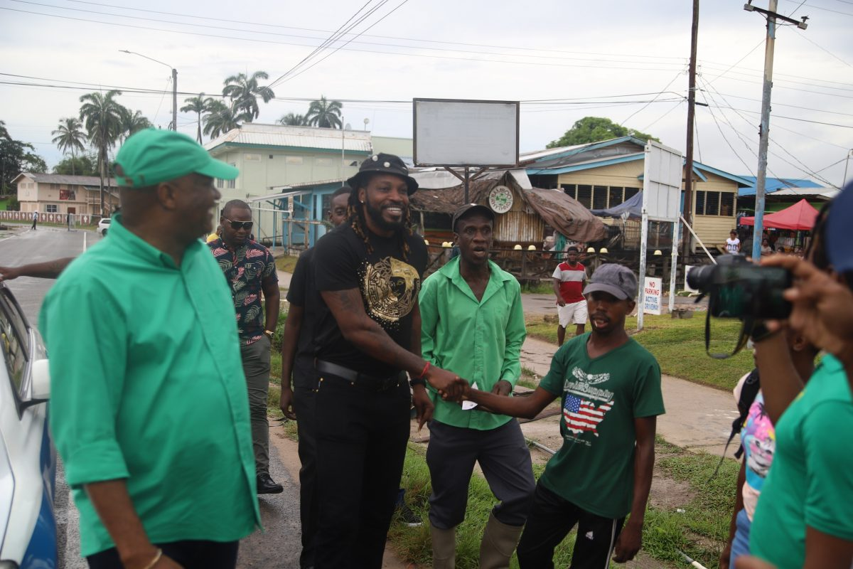 Chris Gayle (centre) greeting fans in Linden on Saturday. At left is Director General of the Ministry of the Presidency, Joseph Harmon. (Terrence Thompson photo)