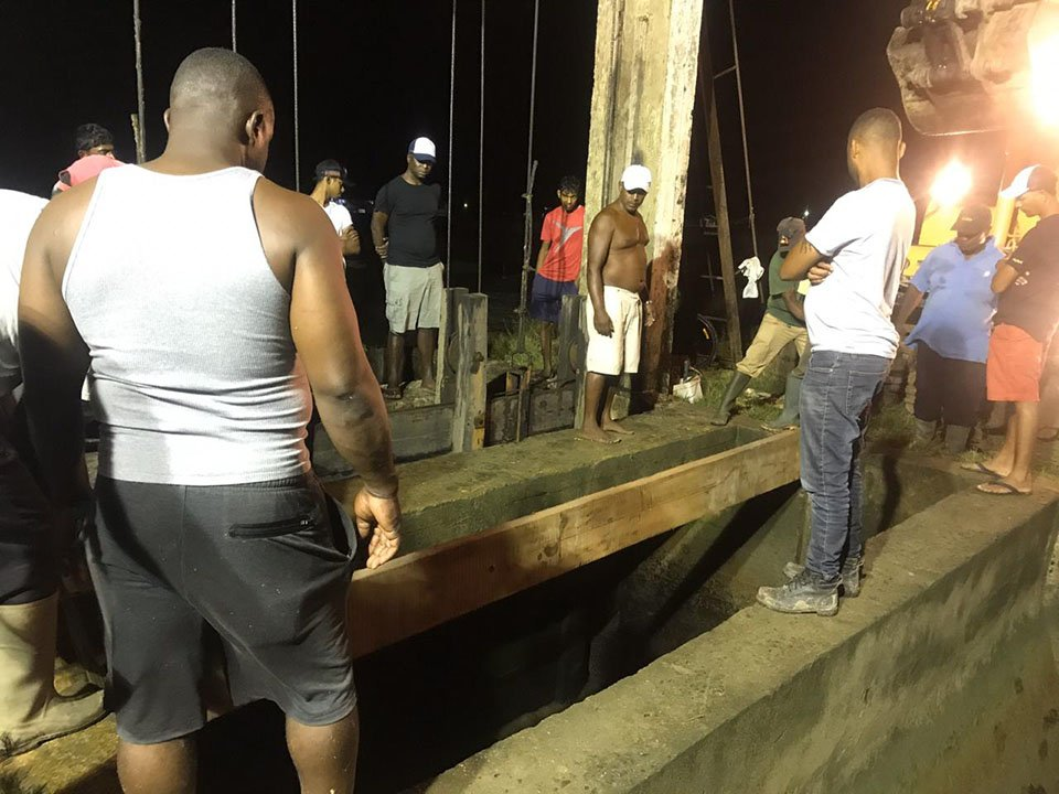 Workers installing a plank as they constructed the temporary door at the Stewartville Koker last night
