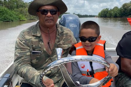 Essequibo Chamber President Roopan Ramotar with his son Roopan (Jr.) on the Capoey Lake