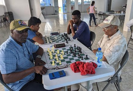 Since the Gaico Construction accumulated chess competitions began, Kenrick Braithwaite (at left in foreground) has been a feature at the tournaments. Win, lose or draw, Braithwaite plays on with an exuberant spirit. In the photo, he faces Errol Tiwari at the National Aquatic Centre, Liliendaal. (Photo by John Lee)