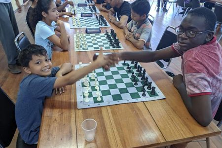 In competitive chess, sometimes the younger play the older and the weak play the strong. The younger is not necessarily the weaker player, especially in this era where young people have technological aides. Garry Kasparov and Magnus Carlsen became world chess champions in their early 20. In photo, Mahir Rajkumar (first, left) of Mae's Schools, shakes hands with Oluwadare Oyeyipo, of Marian Academy, at the Topco Junior Rapid Chess Tournament last Sunday. The handshake is compulsory before the start of every chess game. (Photo by John Lee)