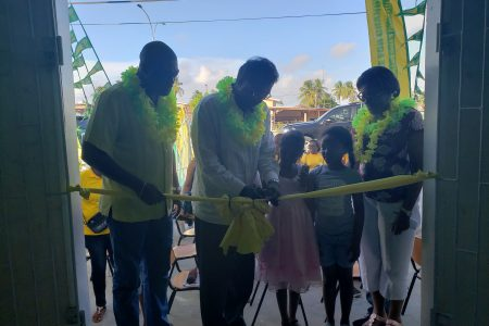 AFC Leader Khemraj Ramjattan along with Minister David Patterson and Minster Catherine Hughes and two children during the cutting of the ribbon to open the new office.