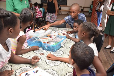 These children are eagerly opening their STEM Guyana Robotics toolkit. (Ministry of the Presidency photo)