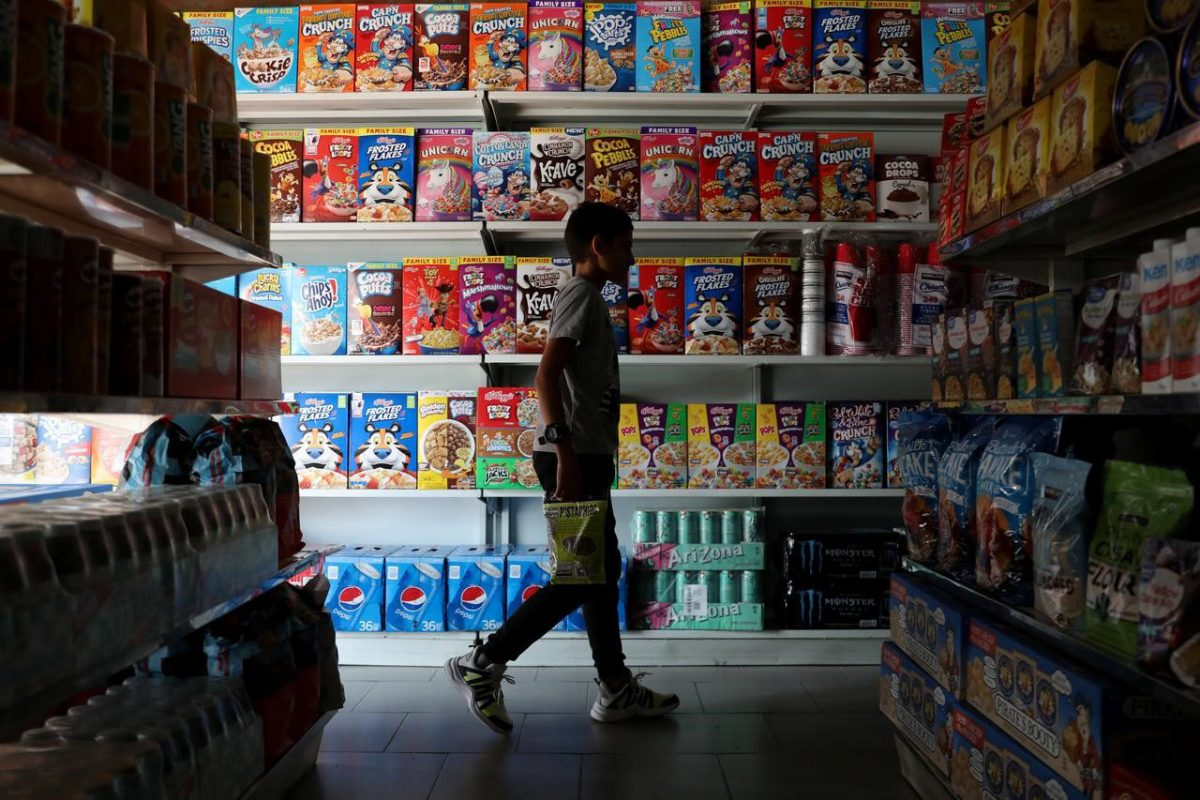"A childpasses in front of a shelf with cereal boxes at a ""bodegon"" named ""Mini Walmart"" in Puerto Cabello, Venezuela December 10, 2019. REUTERS/Manaure Quintero"