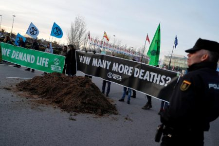 Climate change activist of Extinction Rebellion hold banners after unloading a truck filled with horse excrement in front of U.N. Climate Change Conference (COP25) in Madrid, Spain, yesterday. (REUTERS/Nacho Doce)