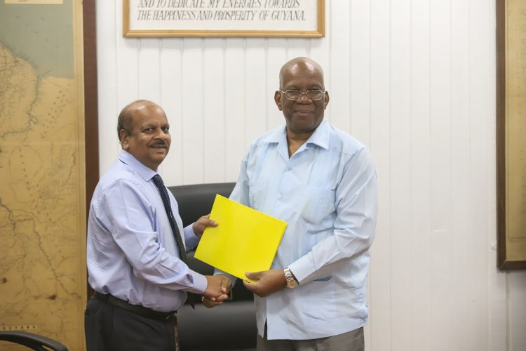 Governor of the Bank of Guyana Dr. Gobind Ganga displays the agreement with Finance Minister Winston Jordan after the signing. (Ministry of Finance photo)