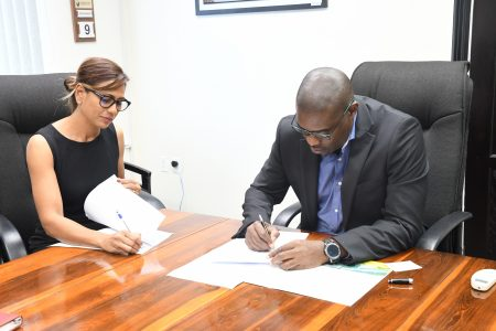 Director of Paws for a Cause-Guyana Marcia Tucker and Minister of Public Infrastructure David Patterson signing the MoU last Monday (Ministry of Public Infrastructure photo)
