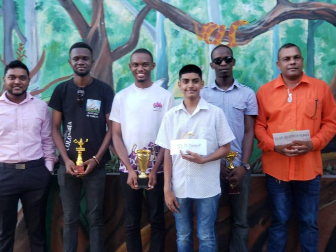 Manager of Outback Adventures Yuvindra Sookraj, sponsor of the Berbice Rapid Chess Tournament (left) with the winners of last Sunday's Berbice Tournament. Standing next to Sookraj are (from left ) Davion Mars (third), Anthony Drayton (first), Omesh Dyal (Best Junior), Wendell Meusa (second) and Kriskal Persaud (Best Berbice Player).