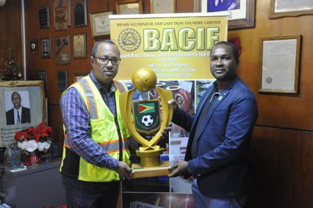 GFF President Wayne Forde [left] collects the Super 16 Championship trophy from Managing Director of BACIF Peter Pompey.