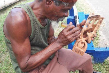 Artist Ras Iah works on his latest piece.