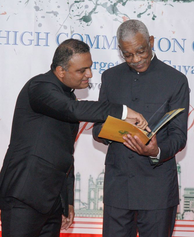 President David Granger [right) and Indian High Commissioner to Guyana Dr. KJ Srinivasa browse commemorative stamps issued by the Government of India on the occasion of the 550th birth anniversary of Guru Nanak Devji. The stamps were presented to President Granger on Sunday evening at the reception. (Ministry of the Presidency photo)