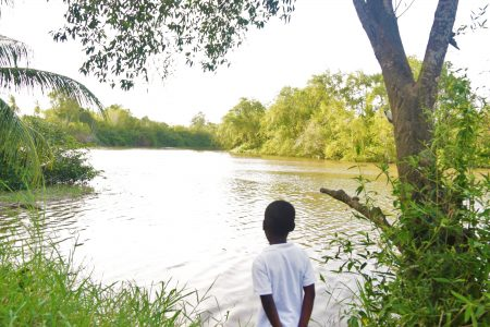 In the shade of the trees, Juliet Moriah's grandson Samuel enjoys the view. The Canje River runs alongside Sandvoort and is only a stone's throw away from the houses of the residents.