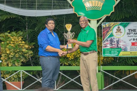 President David Granger presents a cheque and trophy to West Demerara's Taffin Khan for winning the President's 50th Anniversary Shield Rapid Chess Tournament at State House which was held on Saturday, February 22.