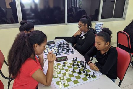 Sisters! Waveney Johnson (left) competing against her sister Nellisha Johnson in the 2020 National Chess Qualifiers Championship at the National Stadium. Both sisters learned to play chess in their hometown of Orealla, Berbice River. Nellisha represented Guyana at the 2018 Chess Olympiad in Georgia. The sisters are competing for a place in this year's Olympiad. (Photo by John Lee)