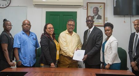 Head of the Interim Management Committee of the GPSU Trevor Benn (third from right) and Chief Labour Officer, Charles Ogle (fourth from right) surrounded by members of the GPSU after the inking of the collective labour agreement. (Department of Public Information photo) .
