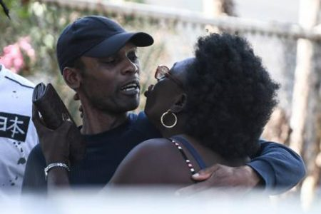 Ann-Marie Williams greets her son with a 'chups' after he and 16 other Jamaicans were deported from the United Kingdom yesterday. The deportees were processed at Harman Barracks and later released.