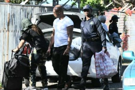 A policeman assists a deported Jamaican with his luggage as he loads them into a vehicle - Ricardo Makyn photo