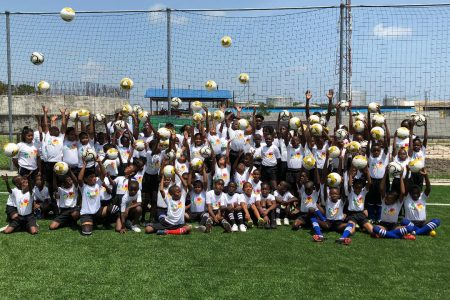 Members of the participating schools posing for the cameras at the start of the GFF Concacaf Next Play Festival at the National Training Center, Providence