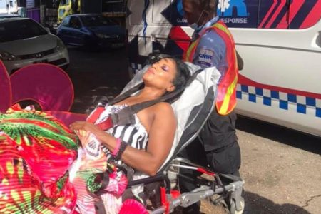Natacha Jones being taken for medical attention after being dragged by truck when he costume got stuck in it yesterday.